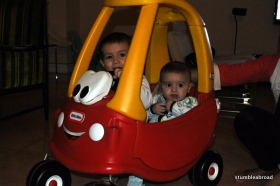 Two boys ride in one very small car.