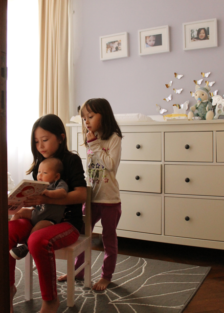 The girls reading to the baby in the super stylish nursery