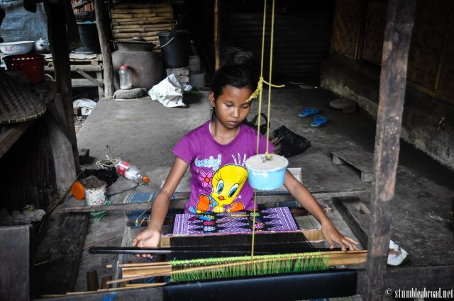 A young girl working on her weaving